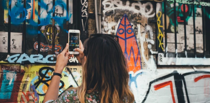a woman taking a picture of an art wall.